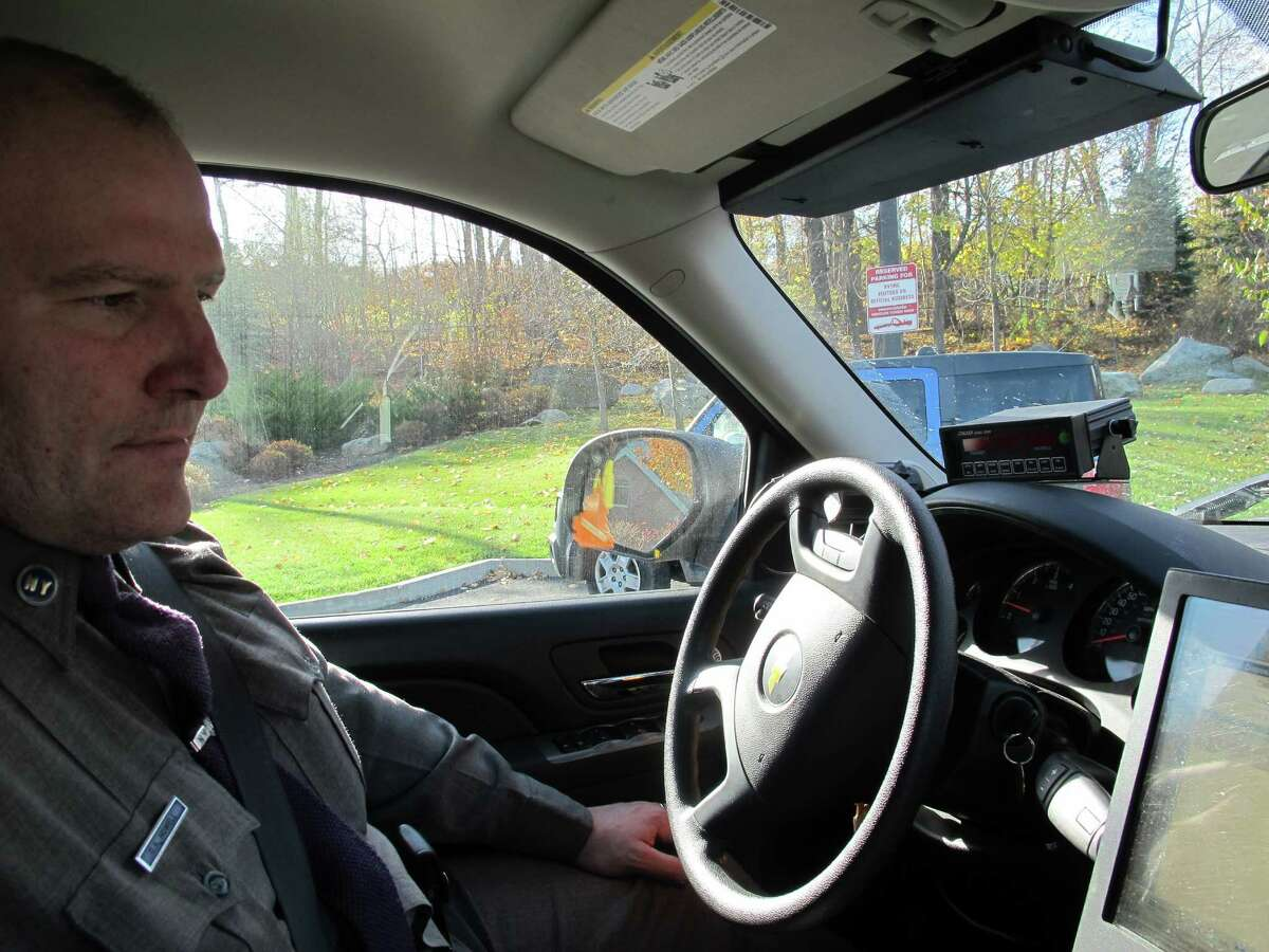 FILE - New York State Trooper Clayton Howell checks a screen that displays driving records inside his patrol vehicle in Hawthorne, N.Y., on Thursday, Nov. 14, 2013. Troopers are using a fleet of tall, unmarked SUVs as part of a crackdown on texting while driving.