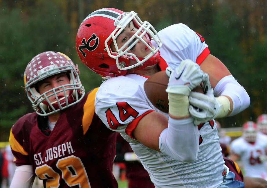 New Canaan's Zachary Allen completes a pass in the endzone for a touchdown, during football action against St. Joseph in Trumbull, Conn. on Saturday, November 1, 2014. At left is St. Joseph's Lars Pedersen. Photo: Christian Abraham / Connecticut Post