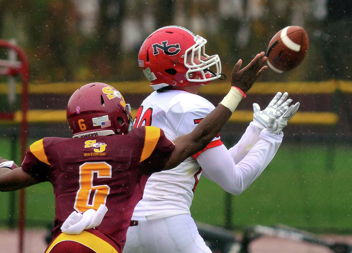 New Canaan's Kyle Smith catches a pass in the endzone for a touchdown, during football action against St. Joseph in Trumbull, Conn. on Saturday, November 1, 2014. Reaching in for the block is St. Joseph's Mufasha Abdul-Basir.