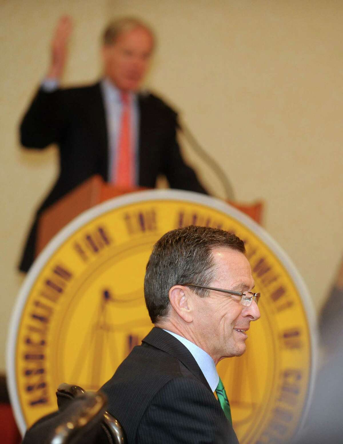 Gov. Dannel P. Malloy listens to Republican challenger Tom Foley speak Saturday, Nov. 1, 2014, during an NAACP Get Out the Vote rally at the Holiday Inn in Bridgeport, Conn.