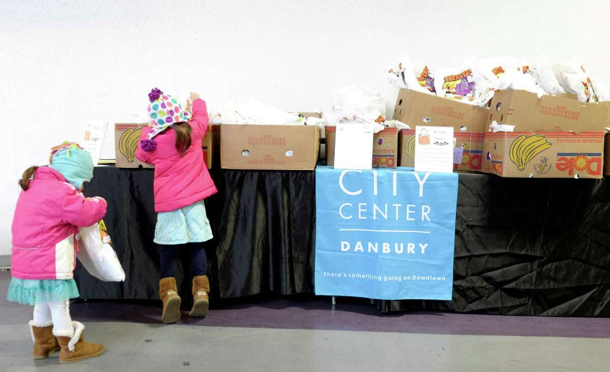 """Emma Lofaro, 3, of New Fairfield, checks out her goodie bag while her sister Hailey Lofaro, 5, stands on tip toes to reach the goodie bag she wants after the CityCenter Danbury """"Halloween on the Green"""" was cancelled because of the weather. The goodie bags to be handed out at the event were available to be pickup up in the Danbury Ice Arena, Danbury, Conn, on Saturday, November 1, 2014."""