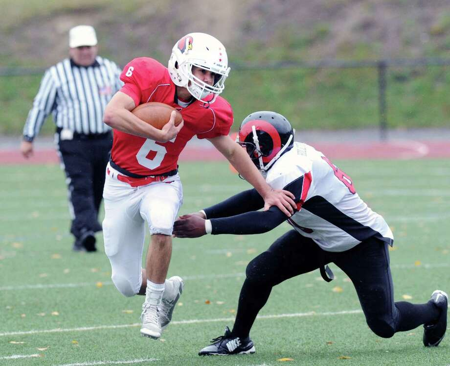 Greenwich quarterback Frank Alfano (#6), left, gets past a Bridgeport Central defender during a running play in the high school football game between Greenwich High School and Bridgeport Central High School at Greenwich, Conn., Saturday afternoon, Nov. 1, 2014. Photo: Bob Luckey / Greenwich Time