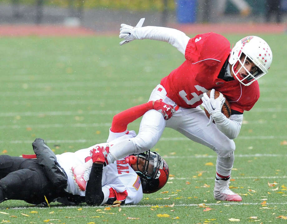 At right, Austin Longi of Greenwich is tackled by Bridgeport Central's Manny Lavant during the high school football game between Greenwich High School and Bridgeport Central High School at Greenwich, Conn., Saturday afternoon, Nov. 1, 2014. Photo: Bob Luckey / Greenwich Time
