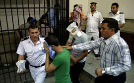 "One of eight Egyptian men guilty of ""inciting debauchery"" covers his face as he exits a court cage."