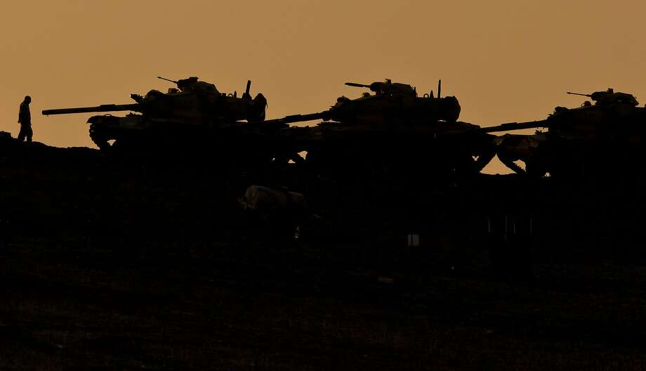 A Turkish soldier walks next to tanks stationed on a hillside overlooking the Syrian city of Kobani on the outskirts of Suruc, Turkey, on the Turkey-Syria border, just across from Kobani, Saturday, Nov. 1, 2014. Tens of thousands of Kurds are rallying in Turkish cities in solidarity with the embattled Syrian city of Kobani, which has been under a brutal siege by the Islamic State group. Photo: Vadim Ghirda, Associated Press