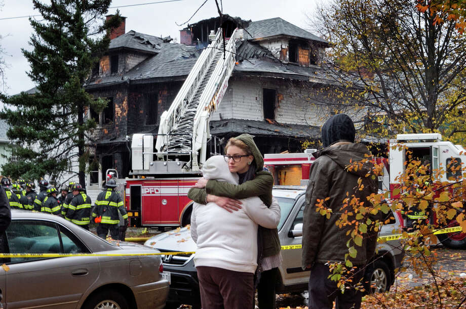 Friends of a victim of the fire console one another. The apartment building is near the University of Southern Maine's commuter campus in Portland, Maine. Photo: Robert F. Bukaty / Associated Press / AP