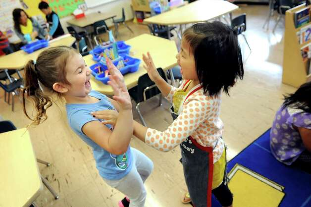 Allura Gogan, 5, left, and Chloe To, 5, give each other a High Ten in the ESL kindergarten class on Tuesday, Sept. 30, 2014, at Shaker Elementary School in Loudonville, N.Y. (Cindy Schultz / Times Union) Photo: Cindy Schultz / 10028785A