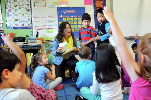 Kindergarten teacher Theresa DiMarino, left, joins Ari Mohammed, 5, center, and Lionel Zheng, 5, at the front of in an ESL classroom on Tuesday, Sept. 30, 2014, at Shaker Elementary School in Loudonville, N.Y. (Cindy Schultz / Times Union) Photo: Cindy Schultz / 10028785A