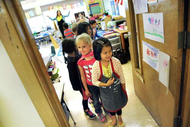 ESL kindergartners Chloe To, 5, right, and Peyton Schrom, 5, center, prepare to lead the class to the music room on Tuesday, Sept. 30, 2014, at Shaker Elementary School in Loudonville, N.Y. (Cindy Schultz / Times Union) Photo: Cindy Schultz / 10028785A