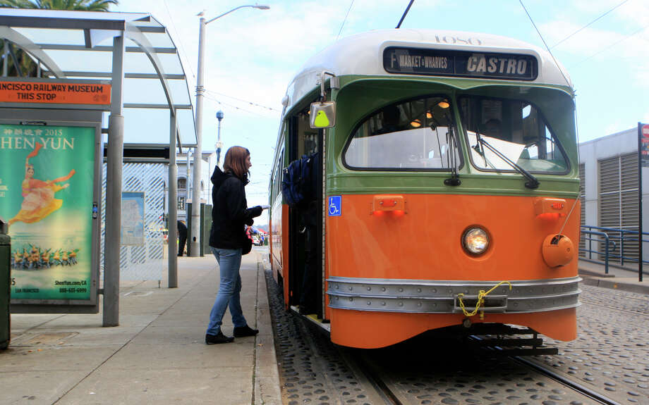 Passengers board a vintage Muni get a chance to take a ride on a vintage muni train around the city and back for free at the Muni Heritage Weekend Celebration in front of the Ferry building in San Francisco, Calif., on Saturday November 1, 2014. Photo: Daniel E. Porter / The Chronicle / ONLINE_YES