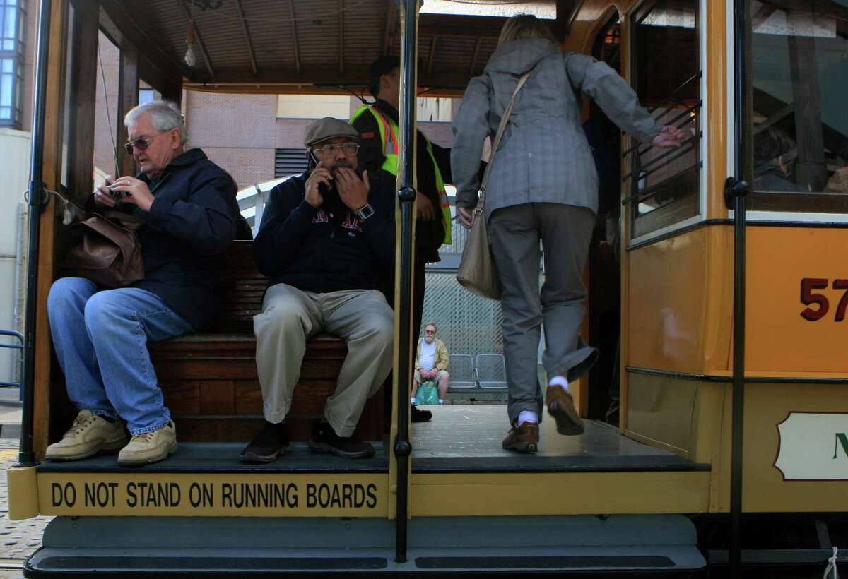 People get on a heritage trolly to take a trip around the city for free at the Muni Heritage Weekend Celebration in front of the Ferry building in San Francisco, Calif., on Saturday November 1, 2014.