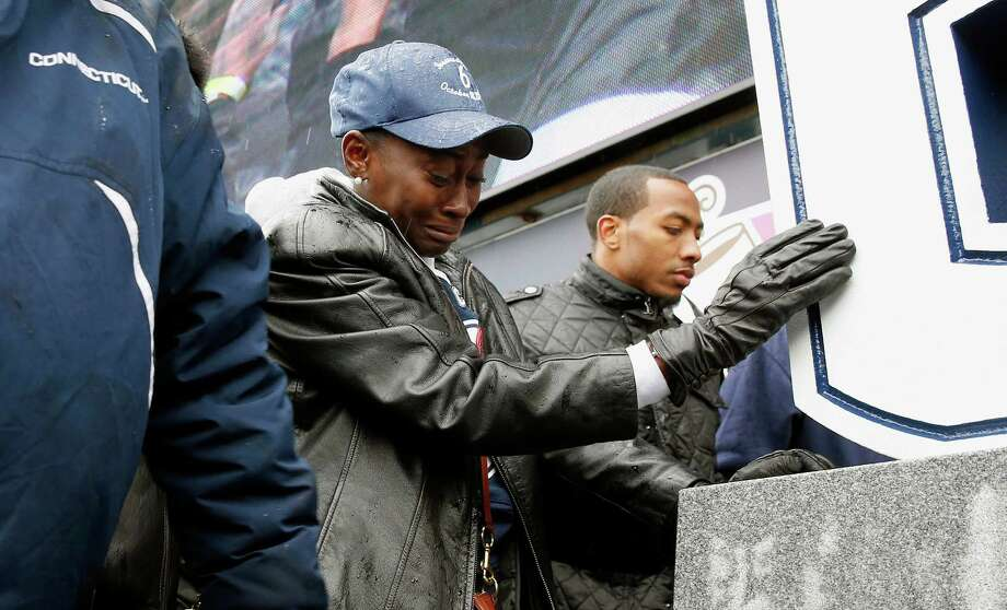 Joangila Howard, center, touches a memorial to her son, former Connecticut plyaer Jasper Howard after its unveiling during halftime at an NCAA college football game against Central Florida in East Hartford, Conn., Saturday, Nov. 1, 2014. (AP Photo/Michael Dwyer) Photo: Michael Dwyer, Associated Press / Associated Press