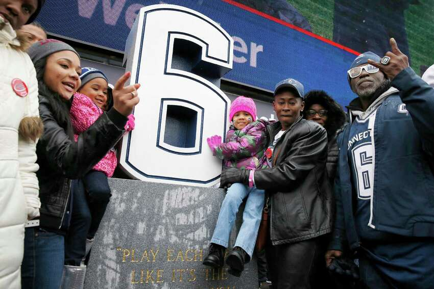 Relatives of former Connecticut player Jasper Howard, including step father Herny Williams, right, grandmother Vicki Ross, second from right, mother Joangila Howard, third from right, and fiancee Daneisha Freeman, second from left, gather around a memorial to Howard after its unveiling during halftime at an NCAA college football game against Central Florida in East Hartford, Conn., Saturday, Nov. 1, 2014. (AP Photo/Michael Dwyer)