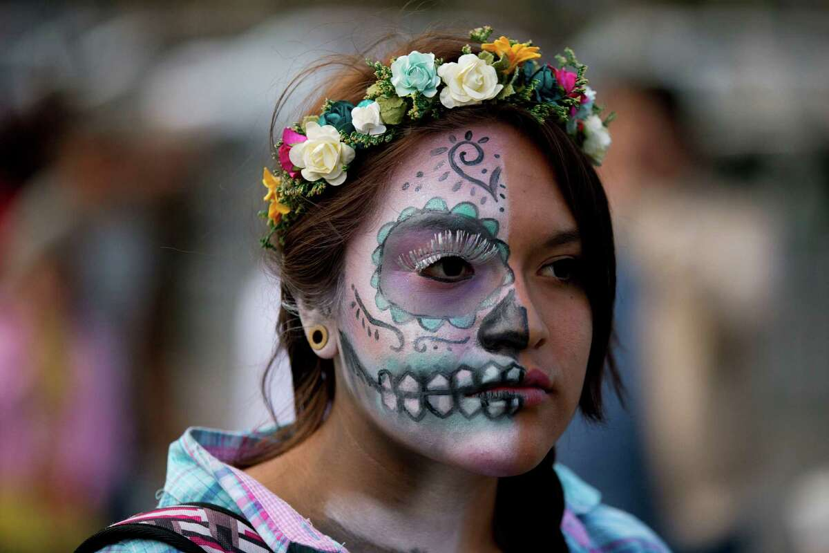 A young woman with her half her face painted as a calavera, visits the Zocalo, where giant skulls and offerings have been erected to mark the holiday, in Mexico City, Friday, Oct. 31, 2014. The Day of the Dead holiday honors the dead as friends and families gather in cemeteries to decorate their loved ones' graves and hold vigil through the night on Nov. 1 and 2.