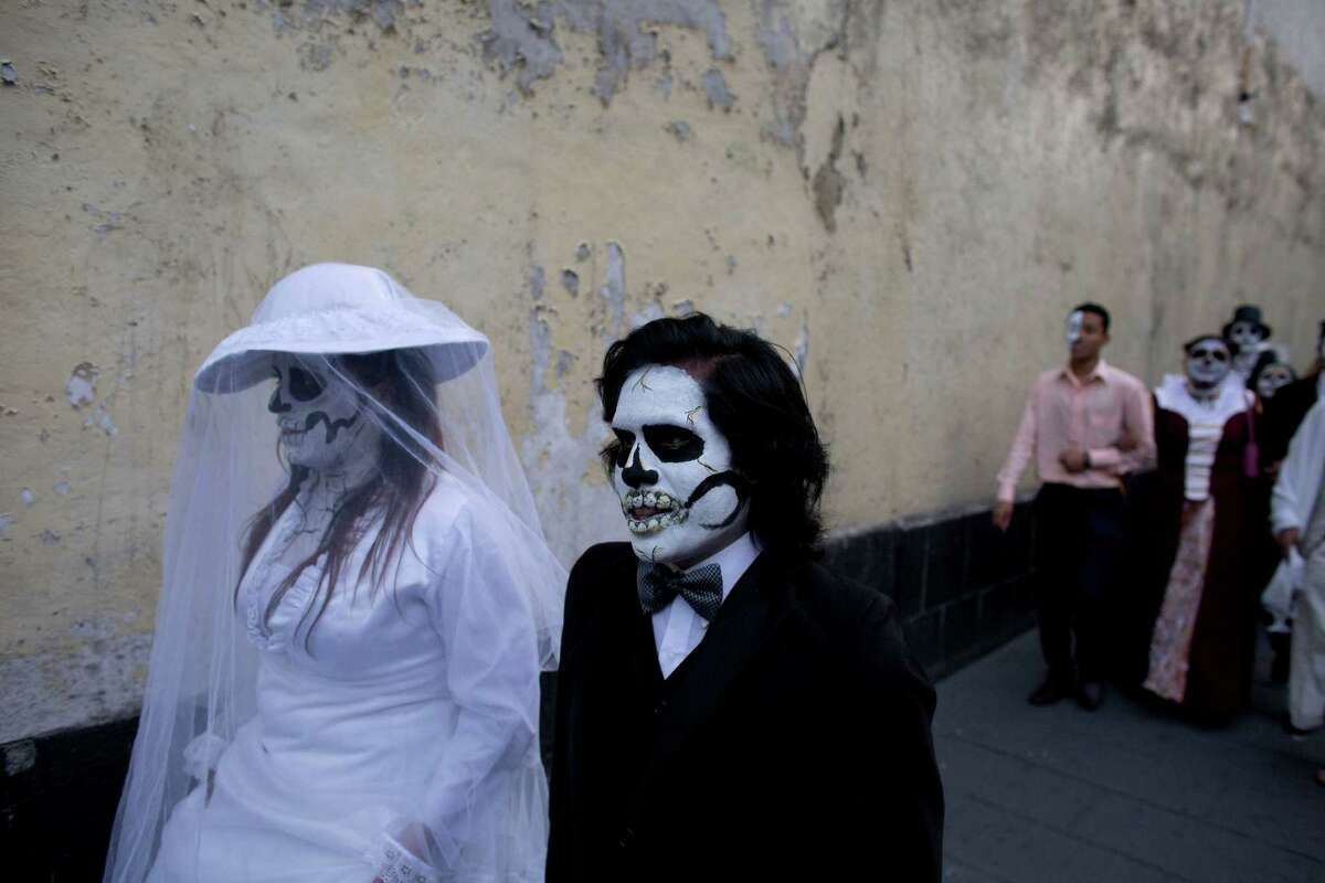 University students wearing Day of the Dead costumes take part in a procession to protest the 43 missing rural college students, in Mexico City, Friday, Oct. 31, 2014. The Day of the Dead holiday honors the dead as friends and families gather in cemeteries to decorate their loved ones' graves and hold vigil through the night on Nov. 1 and 2.
