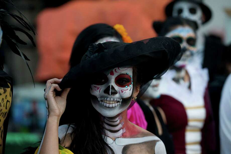 "A young university student dressed as a ""Calavera Catrina"" takes part in a Day of the Dead protest over 43 missing students of a rural teachers college in Mexico Cityon Friday, Oct. 31, 2014. The Day of the Dead holiday honors the dead as friends and families gather in cemeteries to decorate their loved ones' graves and hold vigil through the night on Nov. 1 and 2. Photo: Rebecca Blackwell, AP / AP"