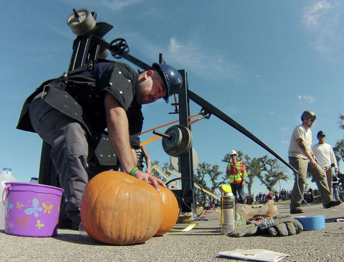 Pablo Ramirez retrieves a pumpkin to be launched by the Society of Women Engineers and American Society of Mechanical Engineers catapult during the sixth annual Monster Mash Pumpkin Smash and STEM Fest at UTSA on Saturday, Nov. 1, 2014. The UTSA College of Engineering and its Student Council held the event to promote engineering to the community. UTSA students designed and built catapults to launch pumpkins for distance and accuracy.