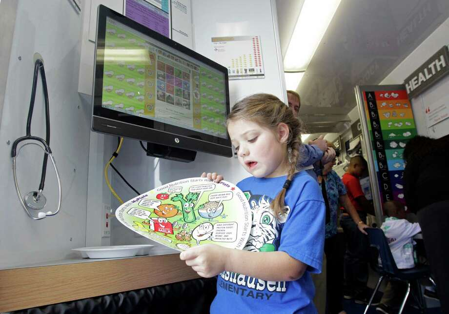 Bailey DePhilippis, 6, a first grader at Bernshausen Elementary, learns about food items from a chart at the nutrition station of the STEAM Express, Klein ISD's new mobile science and technology lab. The trailer is expected to start visiting each of Klein's 40 schools by the end of the year. Photo: Melissa Phillip, Staff / © 2014  Houston Chronicle