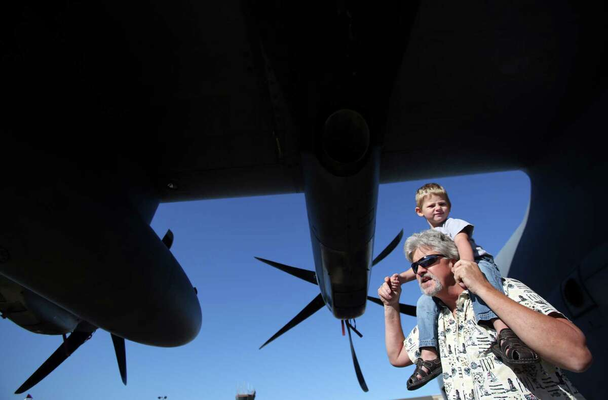 Larry Reed carries grandson Zachary Arnold, 3, as the explore the belly of the aircraft for the Hurricane Hunters, 53rd Weather Reconnaissance SQ, during the Wings Over Houston show at Ellington Field on Saturday, Nov. 1, 2014, in Houston.