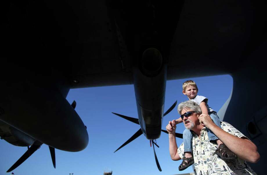 Larry Reed carries grandson Zachary Arnold, 3, as the explore the belly of the aircraft for the Hurricane Hunters, 53rd Weather Reconnaissance SQ, during the Wings Over Houston show at Ellington Field on Saturday, Nov. 1, 2014, in Houston. Photo: Mayra Beltran, Houston Chronicle / © 2014 Houston Chronicle