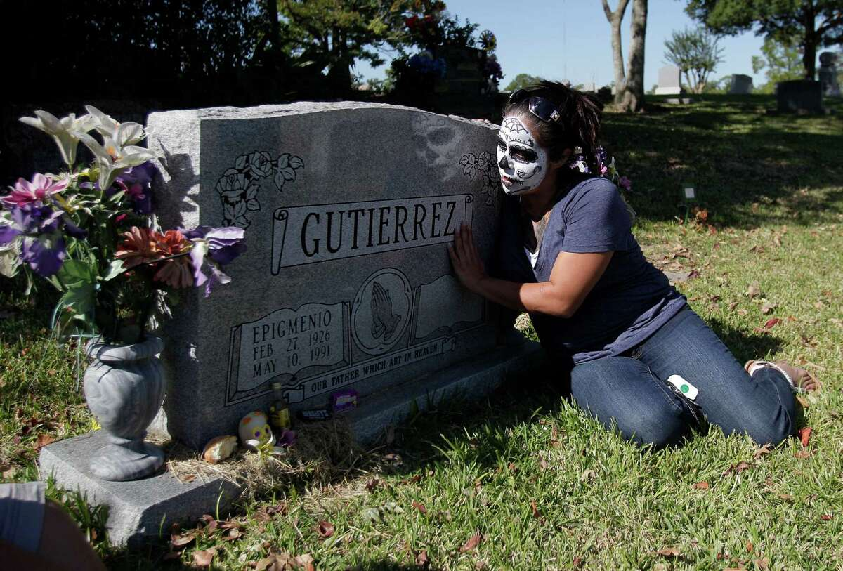 Cristina Cuellar places her hand on her grandfathers grave setting down the offerings, such as candy, tequila, and pan de muerto, in the eve of The Day of the Dead at the Historic Hollywood Cemetery on Saturday, Nov. 1, 2014, in Houston. The Historic Hollywood Cemetery will host a cultural event for the Day of the Dead, Nov. 2nd starting at 10 a.m.