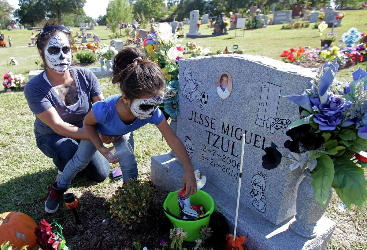Cristina Cuellar holds daughter Andrea Gutierrez as she places down an offering her a close family friend in the eve of The Day of the Dead at the Historic Hollywood Cemetery on Saturday, Nov. 1, 2014, in Houston. The Historic Hollywood Cemetery will host a cultural event Sunday, Nov. 2nd, starting at 10 a.m. in observance of the Day of the Dead.