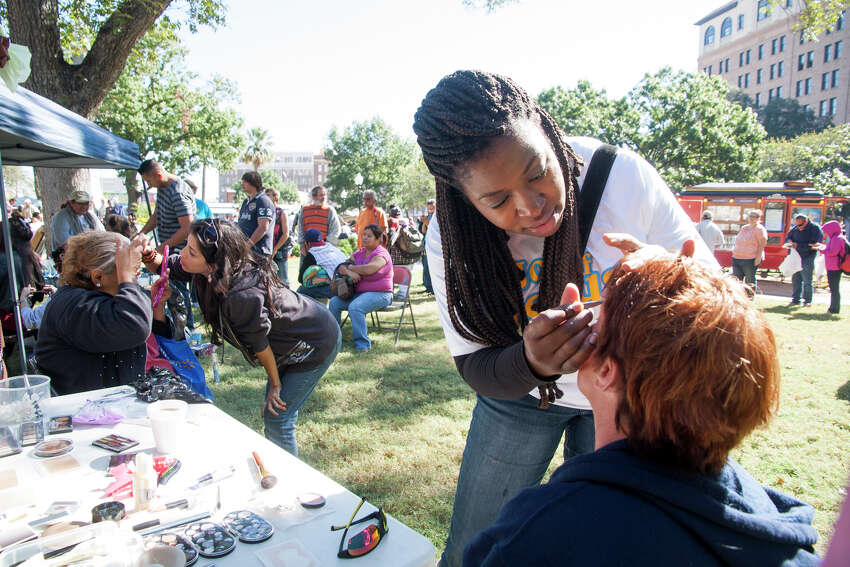 Tanya Workman applies makeup to Tracy May November 1, 2014 during Calvary Chapel of San Antonio 17th annual Joy of Jesus Outreach at Travis Park. The congregation provided more than twenty services for the community including free hair cuts, manicures, and massages.