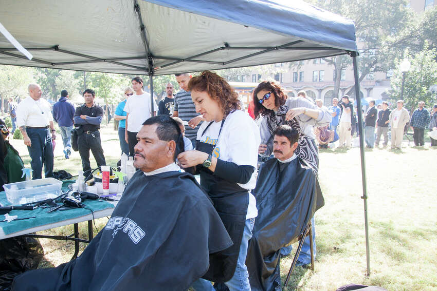 Joce Lara gets his hair cut November 1, 2014 during Calvary Chapel of San Antonio 17th annual Joy of Jesus Outreach at Travis Park. The congregation provided more than twenty services for the community including free hair cuts, manicures, and massages.