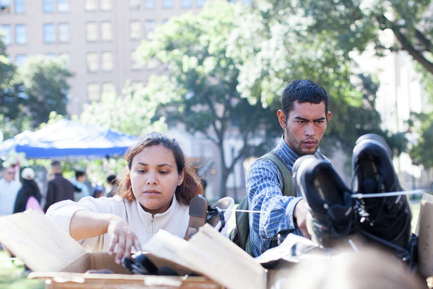 (From left) Anastasia Barrera and Erick Osorio look through boxes filled with shoes November 1, 2014 during Calvary Chapel of San Antonio 17th annual Joy of Jesus Outreach at Travis Park. The congregation provided more than twenty services for the community including free hair cuts, manicures, and massages.