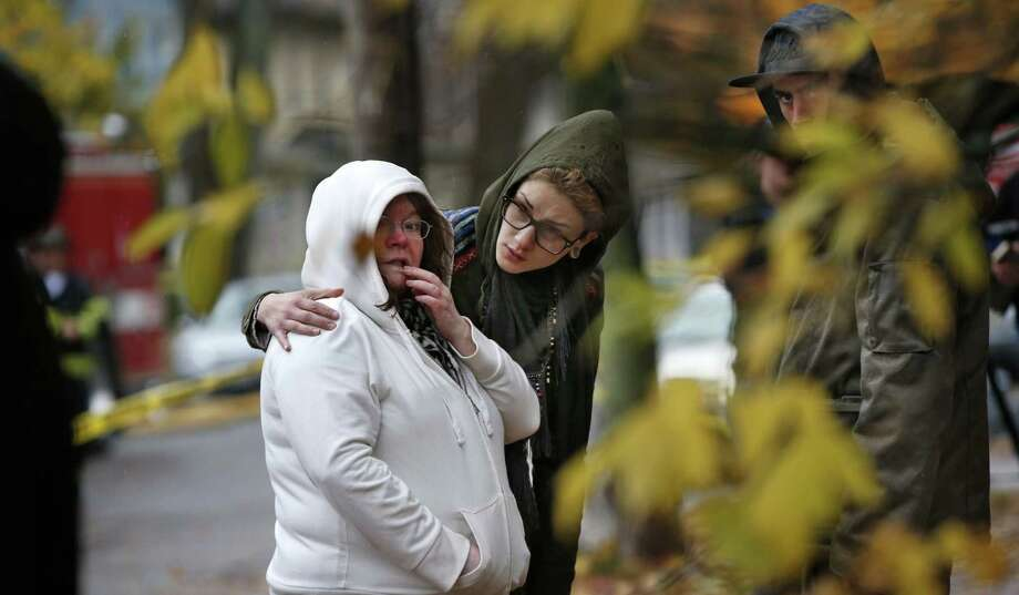 Friends of a victim of the apartment house fire in Portland, Maine, console each other. The heat was so intense at the building, which was gutted, that one early witness had to back away. Photo: Robert F. Bukaty / Associated Press / AP