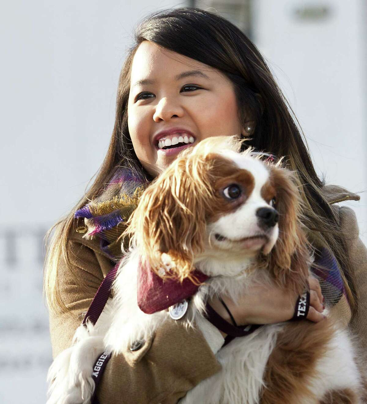 Nina Pham holds up her dog Bentley at Hensley Field in Grand Prairie. Pham, who recovered from Ebola, and the King Charles Spaniel were reunited privately Saturday in a vacant residence where officers once lived at a former naval air base, where he had been quarantined.