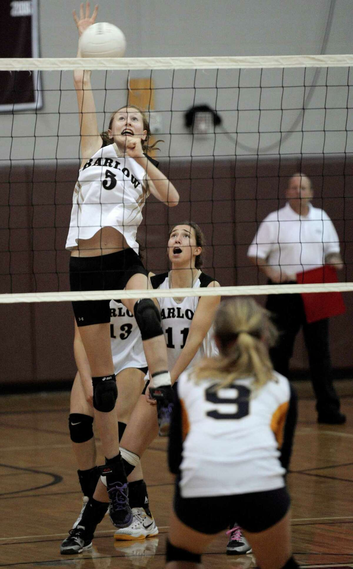 Barlow's Lia Spear (5) spikes the ball over Weston's Melissa Welsh (9) during the SWC girls volleyball Championship match between Weston and Joel Barlow high schools, on Saturday night, November 1, 2014. Barlow's Kaitlyn (13) and Dani Williams (11) are behind Spear.
