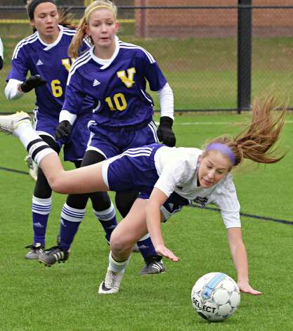 Catholic Central's #3 Lauren Drake, right, takes a tumble as she tries to beat Voorheesville's #6 Julia Hotaling, left, and #10 Laura Patak to the ball during the Section II Class B girls' soccer final at Lansingburgh High School Saturday Nov. 1, 2014, in Troy, NY.  (John Carl D'Annibale / Times Union) Photo: John Carl D'Annibale / 00029265A