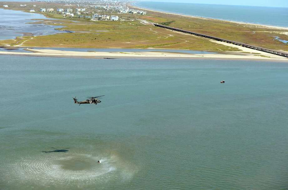 In this photo taken on Wednesday, Oct. 29, 2014, a Black Hawk helicopter hovers above San Luis Pass in Freeport, Texas, as members of the Texas National Guard hoist a Texas Task Force 1 swimmer and diver up out of the water during a three-day swift water rescue training exercise.  (AP Photo/Bryan-College Station Eagle, Sam Craft) MANDATORY CREDIT Photo: Sam Craft, MBR / Bryan-College Station Eagle