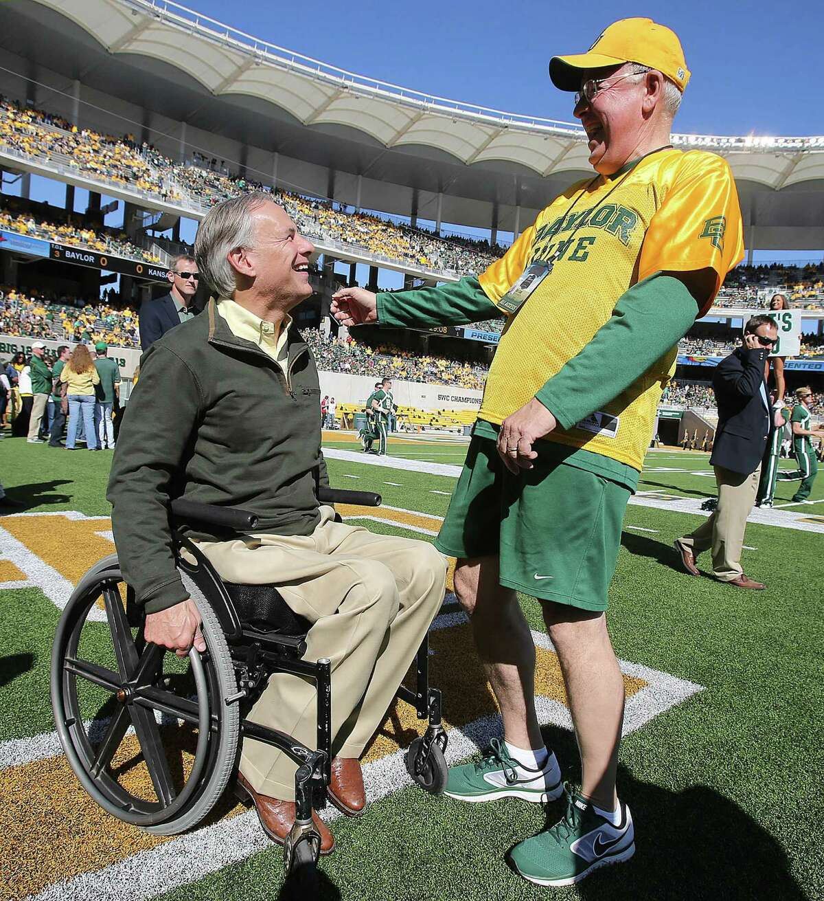 Republican gubernatorial candidate Texas Attorney General Greg Abbott, left, and Baylor President Ken Starr share a laugh at McLane Stadium before the game against Kansas Nov. 1, 2014, in Waco, Texas. (AP photo, Jerry Larson)