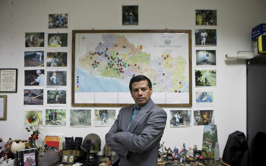 Criminologist Israel Ticas stands by a wall papered with images of his team members at work and a map of El Salvador marking points of reported violent cases. He calls himself  the 'lawyer for the dead.' Photo: Esteban Felix / Associated Press / AP