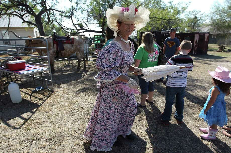 Angel Garcia, wearing her appropriate period costume, participates in the annual Indian Summer Heritage Festival re-enactment of the town of Helena's most famous gunfight, thought to have doomed the town. Photo: Kin Man Hui, Staff / ©2014 San Antonio Express-News