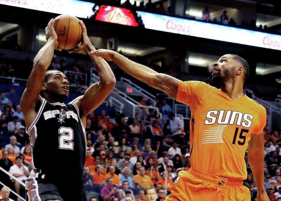 San Antonio Spurs forward Kawhi Leonard (2) shoots against Phoenix Suns forward Marcus Morris (15) in the first quarter of an NBA basketball game, Friday, Oct. 31, 2014, in Phoenix. (AP Photo/Rick Scuteri) Photo: Rick Scuteri, FRE / Associated Press / FR157181 AP