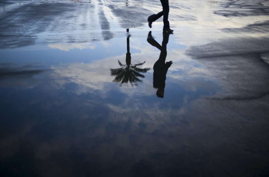 A fan is reflected in a rain puddle they arrive for the Breeders' Cup horse race at Santa Anita Park Saturday, Nov. 1, 2014, in Arcadia, Calif. (AP Photo/Jae C. Hong) Photo: Jae C. Hong, Associated Press