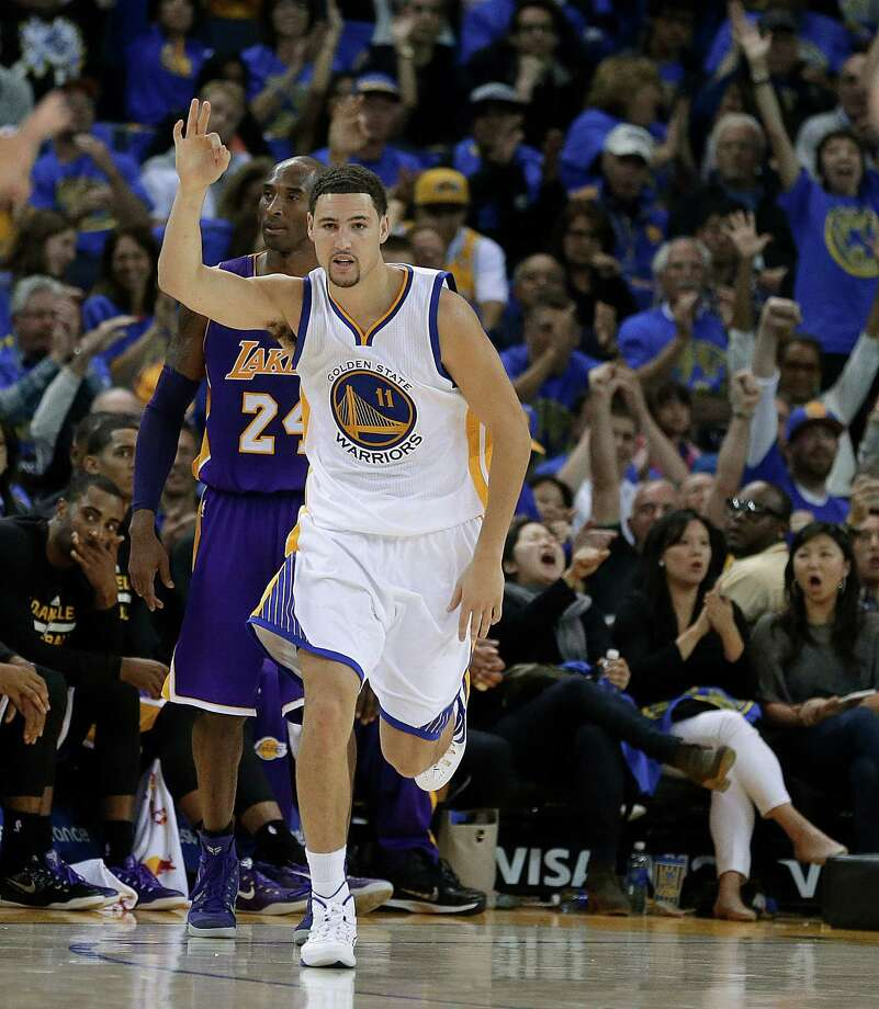 Golden State Warriors' Klay Thompson celebrates past Los Angeles Lakers' Kobe Bryant after scoring during the second half of an NBA basketball game Saturday, Nov. 1, 2014, in Oakland, Calif. (AP Photo/Ben Margot) Photo: Ben Margot / Associated Press / AP