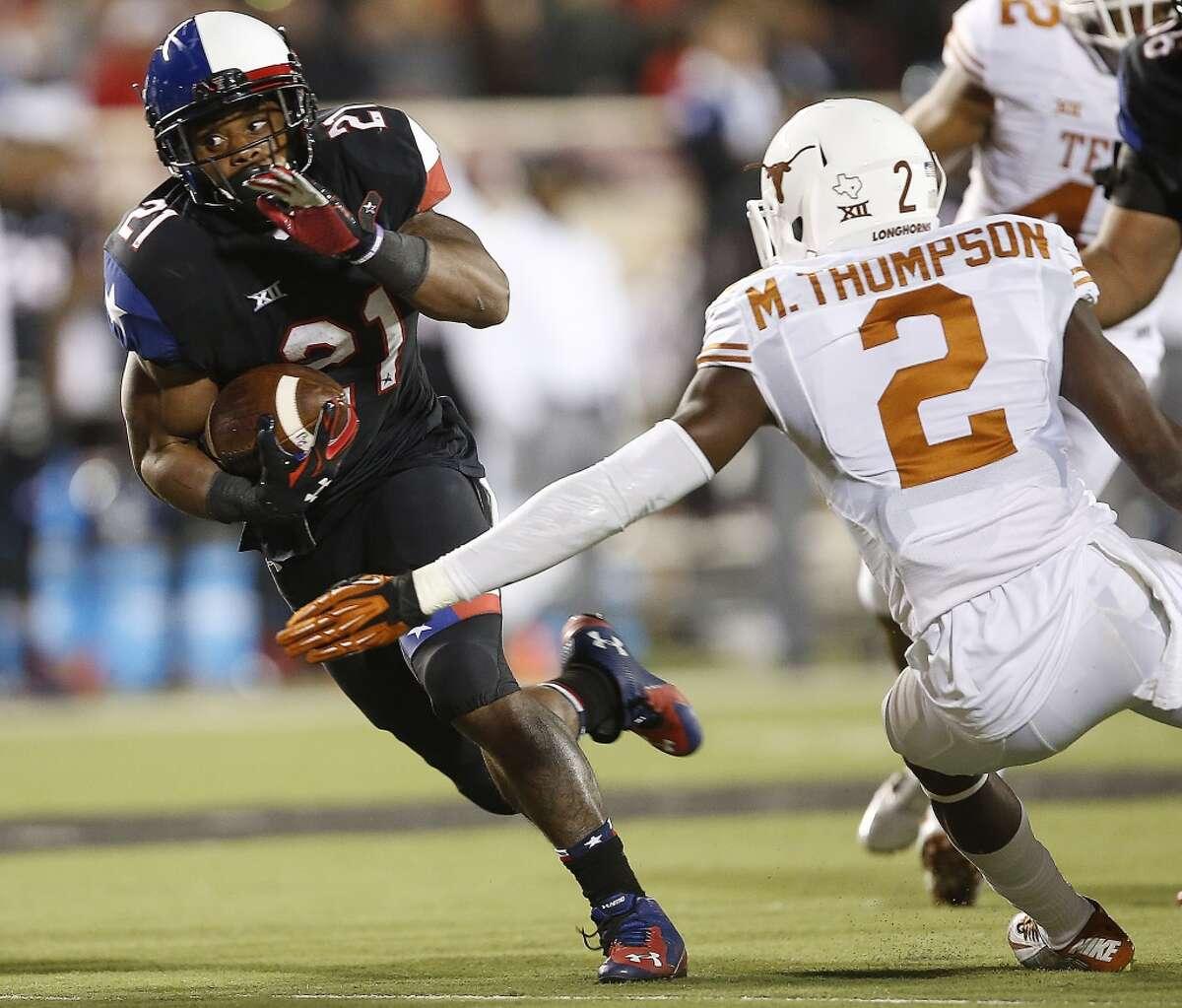 Texas Tech's DeAndre Washington runs past Texas' Mykkele Thompson during an NCAA college football game in Lubbock, Texas, Saturday, Nov. 1, 2014. (AP Photo/Lubbock Avalanche-Journal, Tori Eichberger)