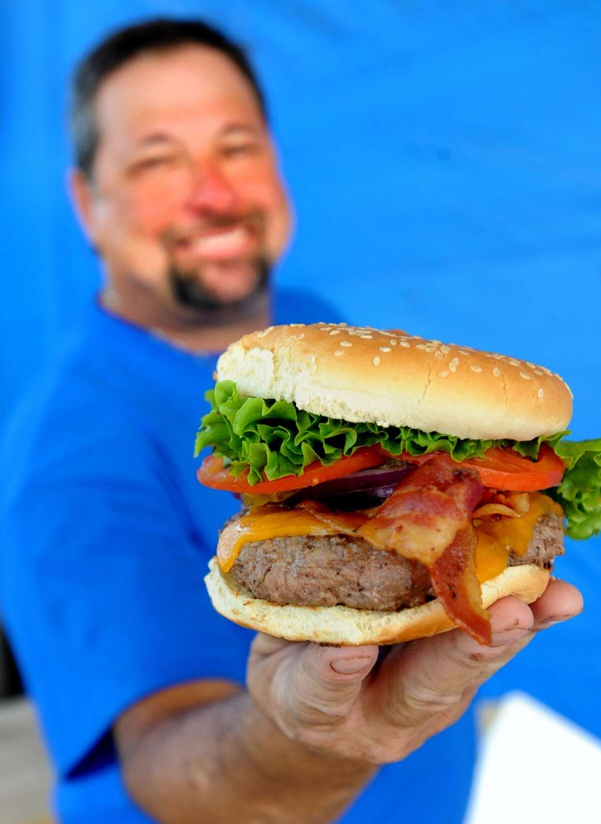 Joe Oates shows off a Boss Burger at Boss Burger on Twin City Highway in Nederland. Photo taken Tuesday, October 21, 2014 Guiseppe Barranco/@spotnewsshooter