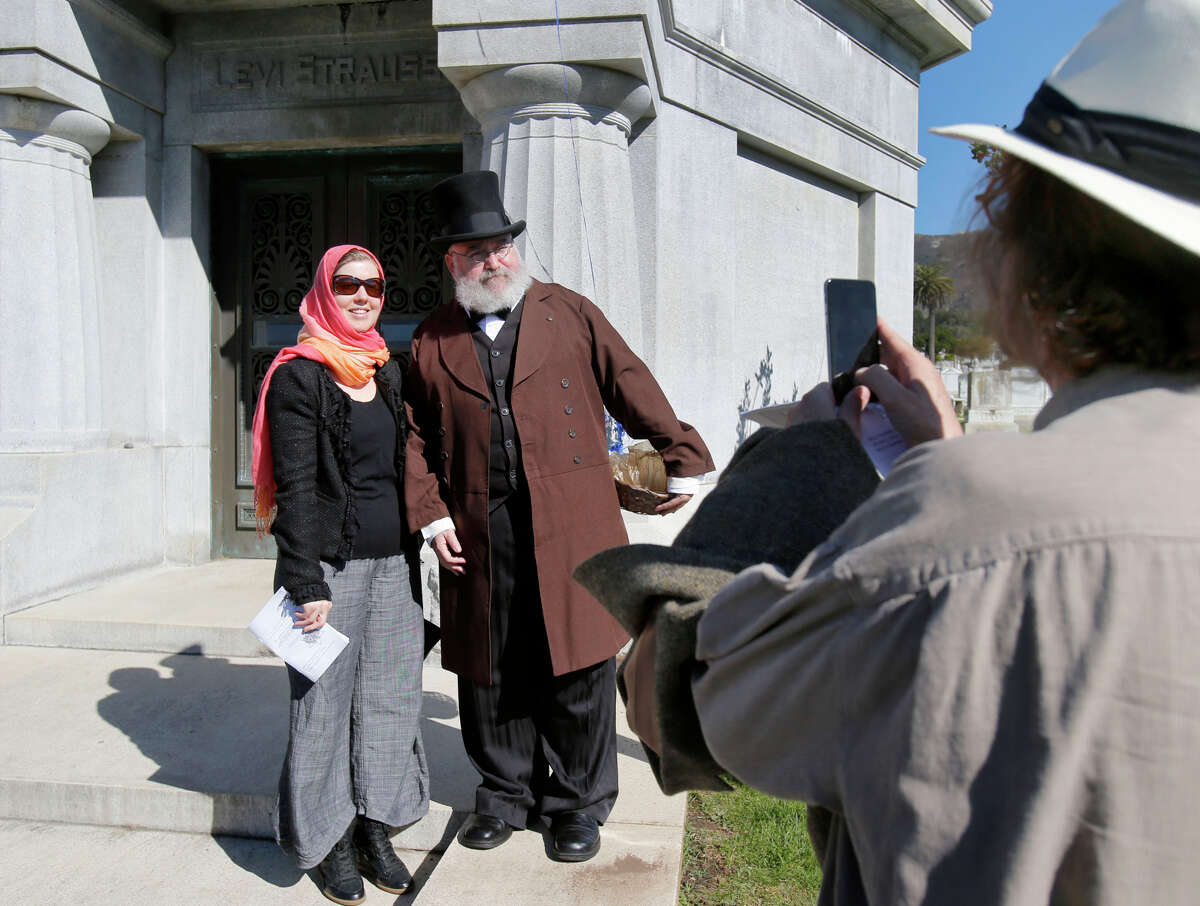 David Martin of Davis takes a picture of and Dena Martin with Daniel Will-Harris, portraying Levi Strauss.