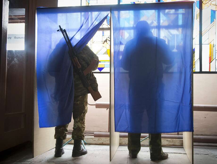 Pro-Russian rebels fill their ballots in voting cabins at a polling station set up inside a rebel military base during rebel elections in the city of Donetsk, eastern Ukraine Sunday, Nov. 2, 2014. The pro-Russian rebels are holding the elections that were dismissed by Ukraine and the West as illegitimate.  (AP Photo/Dmitry Lovetsky) Photo: Dmitry Lovetsky, Associated Press