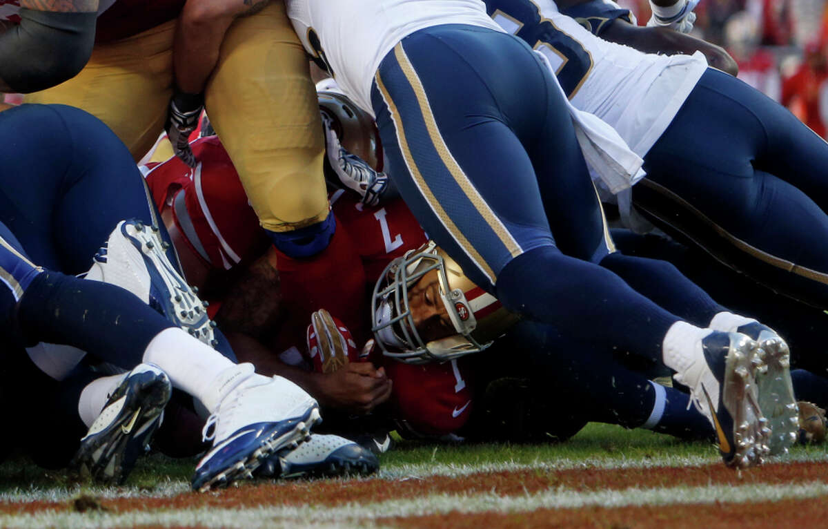 San Francisco 49ers' Colin Kaepernick (7) at the bottom of the pile after fumbling at goal line in final seconds of 13-10 loss to St. Louis Rams during NFL game at Levi's Stadium in Santa Clara, Calif., on Sunday, November 2, 2014.