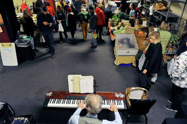 Paul Cronin of Albany plays the piano as he entertains people shopping at the Schenectady Greenmarket inside Proctors on Sunday, Nov. 2, 2014, in Schenectady, N.Y.  The market has now moved inside for the winter months.  (Paul Buckowski / Times Union) Photo: Paul Buckowski / 00029291B
