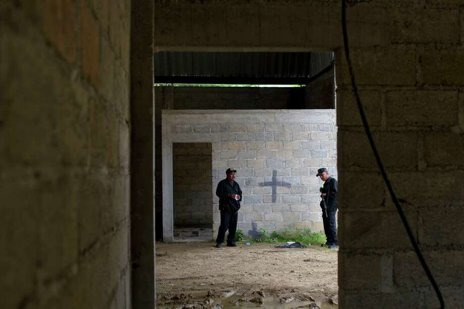 FILE - In this July 3, 2014, file photo, state police stand inside a warehouse where a black cross covers a wall near blood stains on the ground, after a shootout between Mexican soldiers and alleged criminals on the outskirts of the village of San Pedro Limon, in Mexico state, Mexico. Officials said Sunday Nov. 1, 2014, that seven Mexican soldiers have been charged with crimes ranging from homicide to improper conduct in connection with the shooting deaths of suspected gang members at a rural warehouse on June 30. (AP Photo/Rebecca Blackwell, File) Photo: Rebecca Blackwell, STF / AP
