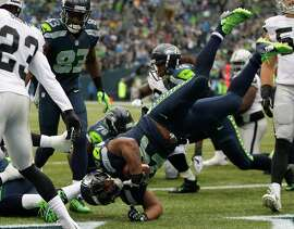 SEATTLE, WA - NOVEMBER 02:  Running back Marshawn Lynch #24 of the Seattle Seahawks flips into the end zone for a touchdown during the first quarter of the game against the Oakland Raiders at CenturyLink Field on November 2, 2014 in Seattle, Washington.  (Photo by Otto Greule Jr/Getty Images)