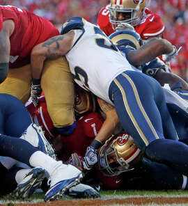 Colin Kaepernick is at the bottom of the goal-line pile. Where the ball is and who had it when are the big questions.