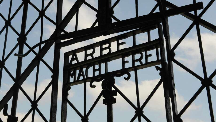 "The slogan on the gate at the former Duchau camp, shown in 2009, translates to ""Work sets your free."" Photo: Christof Stache, STR / AP"
